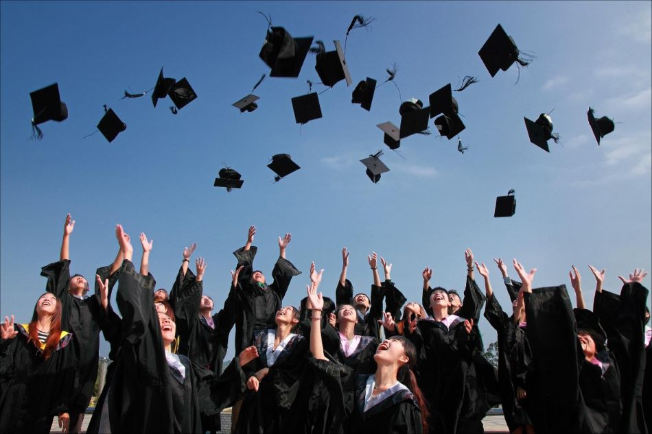 graduating students throwing caps into the air in celebration